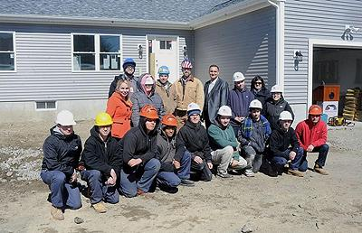 Some of the Diman teachers and students involved in building this year's house for a qualifying first-time homebuyer stand outside the home on Duluth Street in Fall River - Herald News Photo | Dave Souza