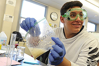 Diman sophomore Ronnie Aguiar shows a visitor the results of an experiment in his biology class.