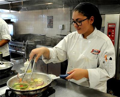 Culinary student Selena Medeiros working at a single burner stove on a hot day at Diman [HN | Dave Souza]