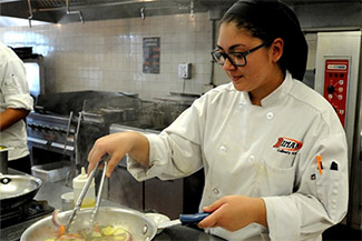 Culinary student Selena Medeiros working at a single burner stove on a hot day at Diman (HN | DS)