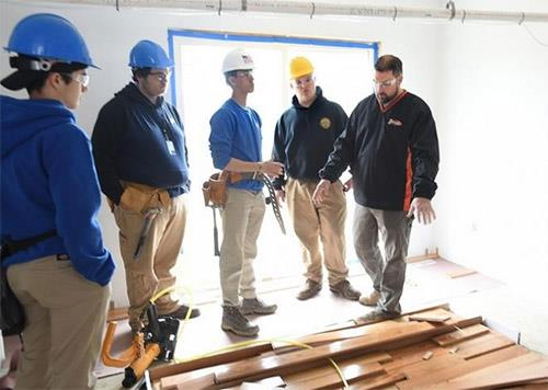 At the outset of their workday, instructor Jeffrey Cabral outlines the process for installing hardwood flooring at this year'