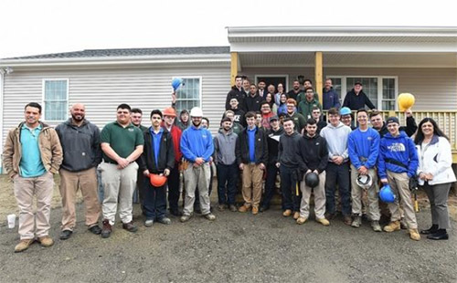 Students and staff pause for a photo during a visit by Mayor Jasiel Correia to this year's Diman house in Fall River