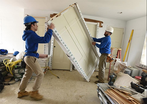 Senior Joshua Demelo, left, and junior Josh Estacio organize doors to be installed at this year's Diman house