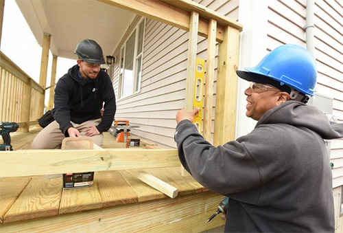Junior Tyler Viveiros, of Fall River, gets some praise for his accuracy from Carpentry instructor Cory Luz as they make and