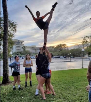 Olivia Motta is held high during this outdoor practice time for the Diman cheerleading team in Orlando, FL, earlier this mont